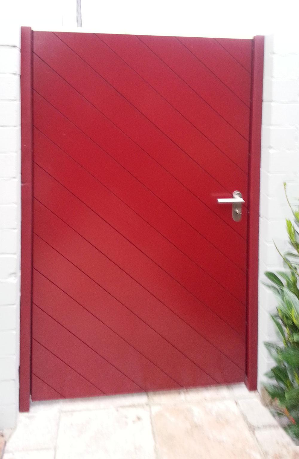 Rote Holztür für den Außenbereich im Mauerdurchgang